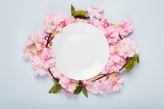 Piso pone flores de flor en la mesa