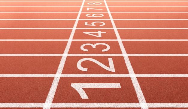 Pista de atletismo del atleta con número en el inicio. vista lateral y ángulo de primer plano.