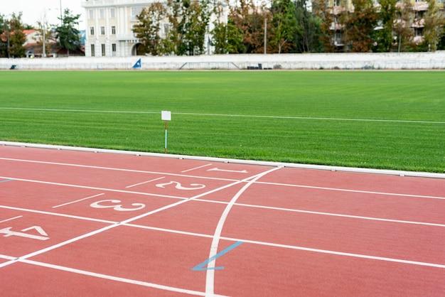 Pista de atletismo con campo de hierba en día soleado