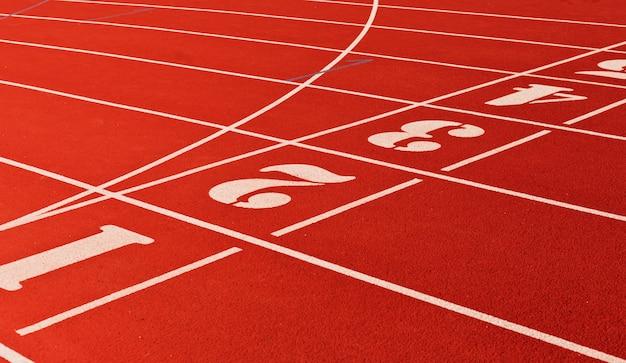 Pista de atletismo del estadio con revestimiento rojo y números closeup