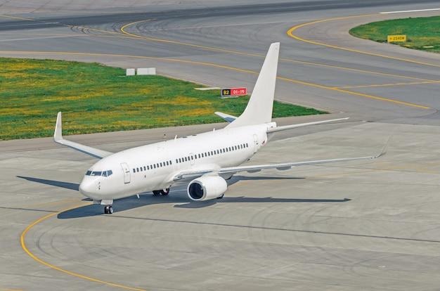 Pista de dirección y pista con un avión en la plataforma del aeropuerto
