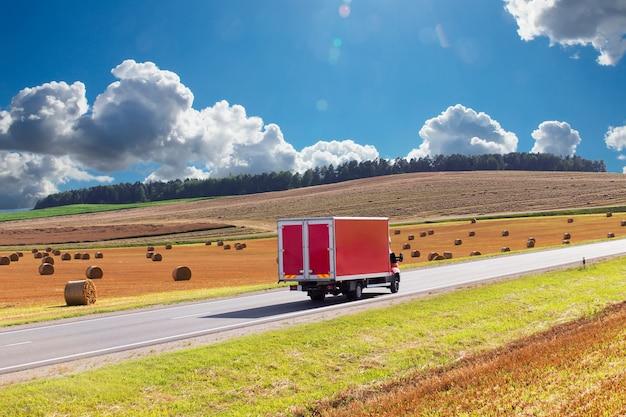 Pista de entrega roja, furgoneta en la carretera, con el telón de fondo de un campo de trigo cosechado amarillo. hay un lugar para la publicidad.