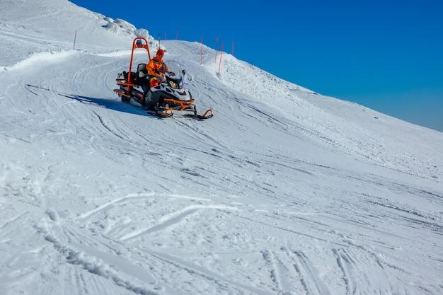 Pista de esquí vacía en tiempo soleado. rescate de montaña en moto de nieve