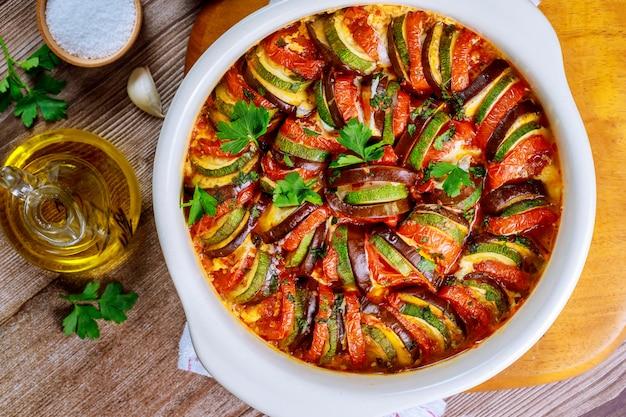 Pisto de verduras cocidas con queso mozzarella en una sartén blanca