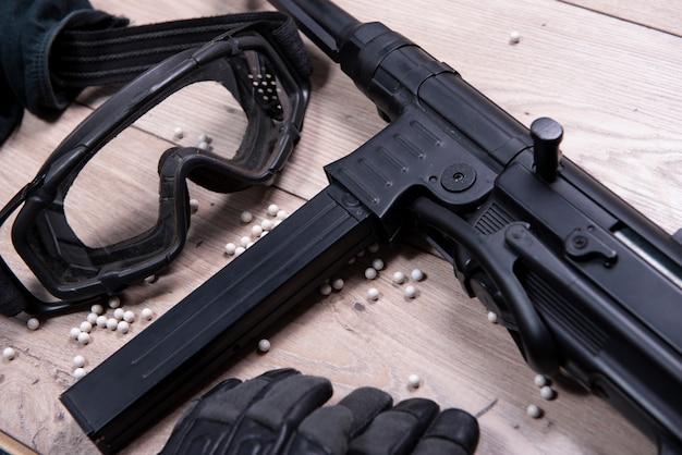 Pistola airsoft con gafas protectoras y muchas balas