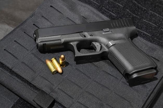 Pistola y balas de 9mm en una chaqueta antibalas.