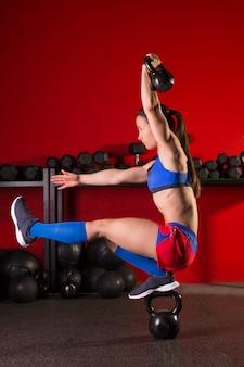 Pistola de mujer kettlebell equilibrio en cuclillas en el gimnasio