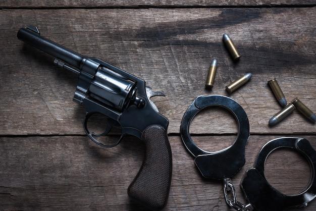 Pistola con municiones y grillete sobre fondo de madera, vista superior