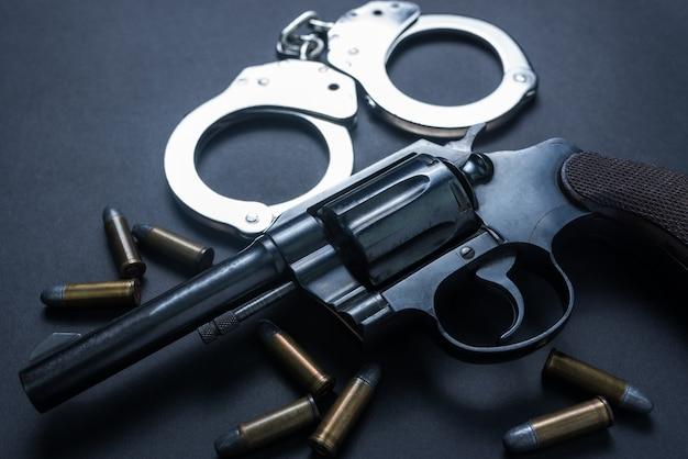 Pistola con municiones y grillete sobre fondo negro.