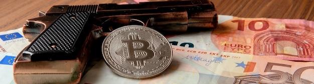 Pistola negra, euro y moneda en forma de bitcoin en madera.