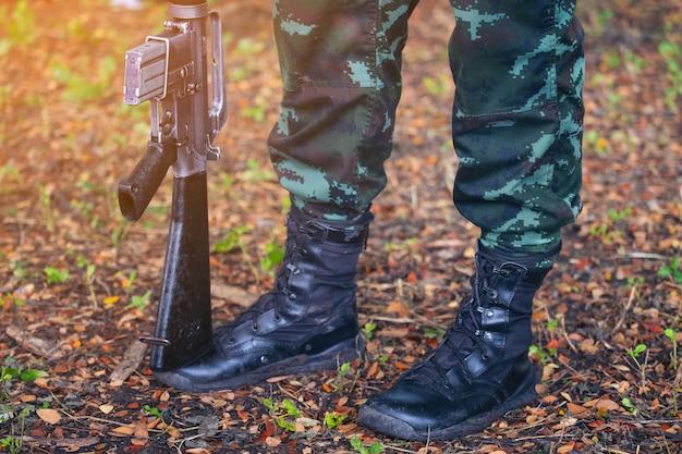 Pistola a pie ejército, botas militares, líneas de comando soldados en uniformes de camuflaje tailandia