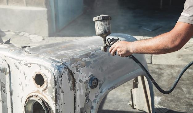 Pistola pulverizadora en la mano de un pintor. pintar los detalles del coche