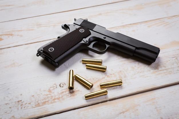 Pistola con rondas en el escritorio de madera