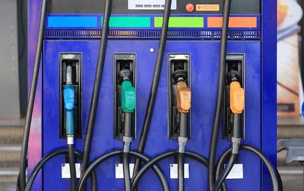 Pistolas de combustible de varios colores en la estación de combustible.