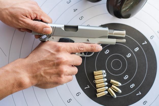 Pistolas con munición sobre papel objetivo.