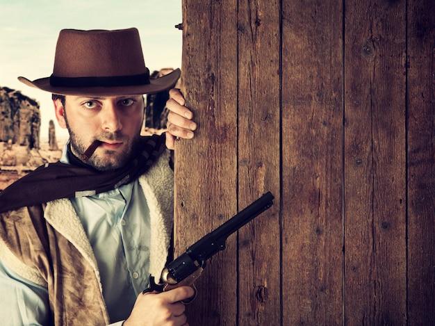 Pistolero malo indica con el arma una tabla de madera