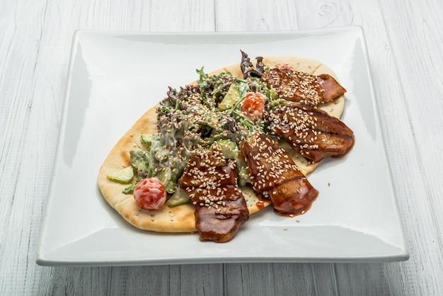 Pita con carne y ensalada de verduras en el plato