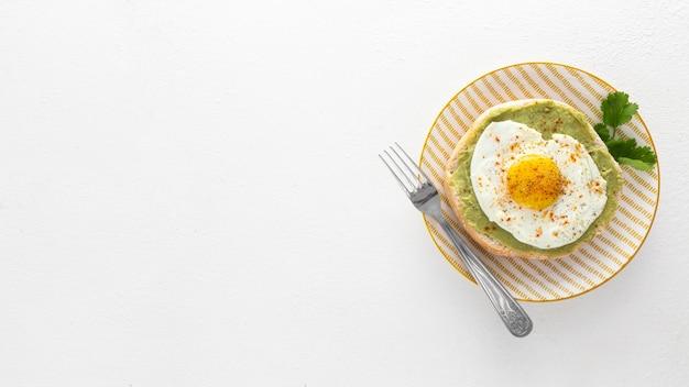 Pita laicos plana con aguacate y huevo frito en un plato con espacio de copia
