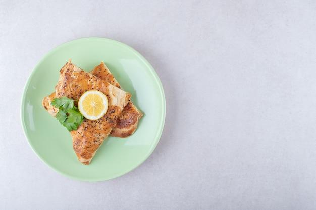 Pita de ramadán con rodaja de limón en un plato, sobre el mármol.