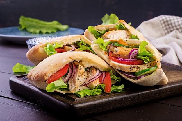 Pita rellena de pollo, tomate y lechuga en madera, cocina del medio oriente.