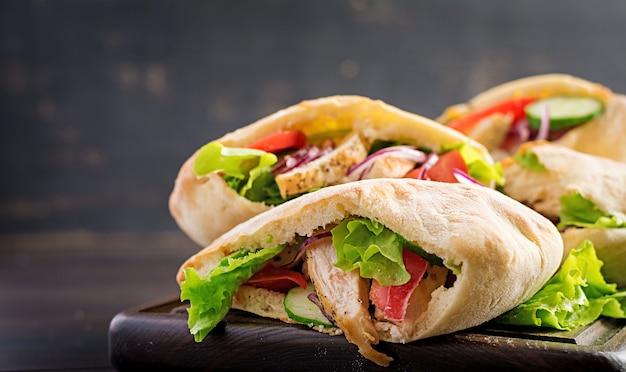 Pita rellena de pollo, tomate y lechuga en la mesa de madera. cocina del medio oriente.