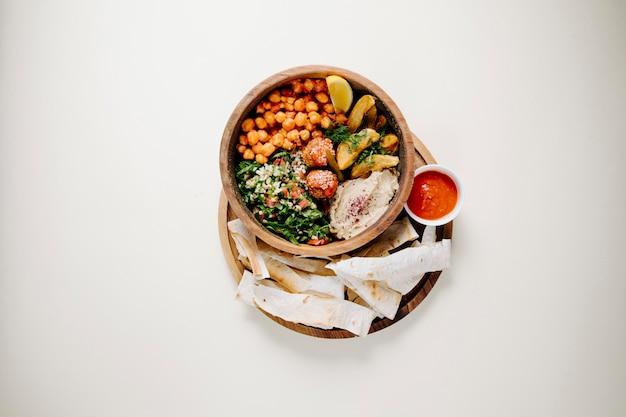 Piti nacional con carne y hierbas dentro del cuenco de cerámica con lavash y salsa de tomate.