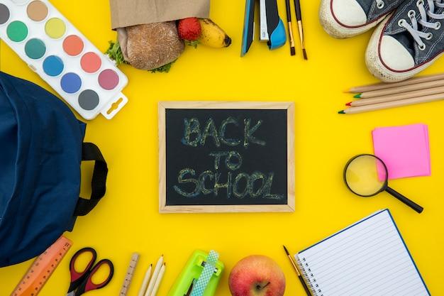 Pizarra con accesorios escolares sobre fondo amarillo