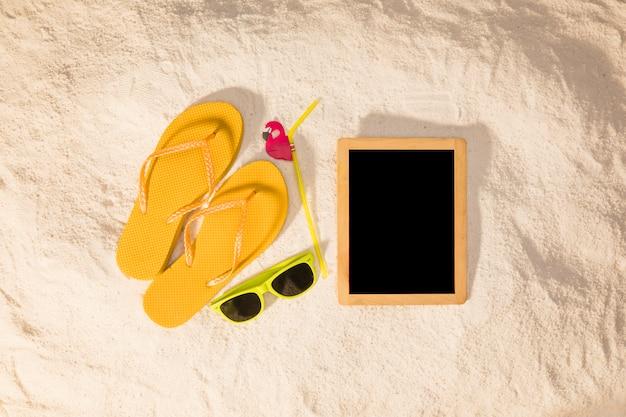 Pizarra y accesorios de verano sobre arena.