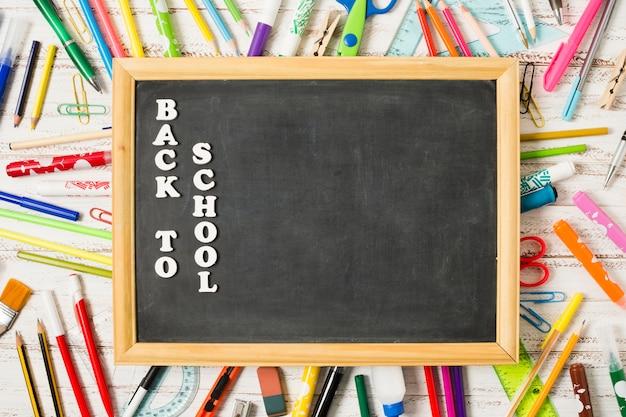 Pizarra aplanada rodeada de útiles escolares.