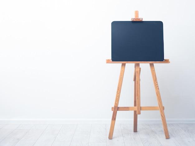 Pizarra de arte en blanco, caballete de madera, vista frontal, contra el fondo de una pared blanca.
