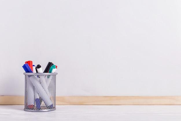 Pizarra blanca, marcadores en el stand sobre la mesa.