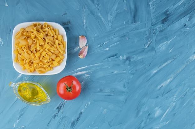 Una pizarra blanca de pasta cruda con aceite y tomates rojos frescos sobre un fondo azul.