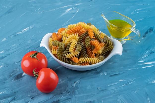 Una pizarra blanca de pasta cruda con aceite y tomates rojos frescos sobre una superficie azul.