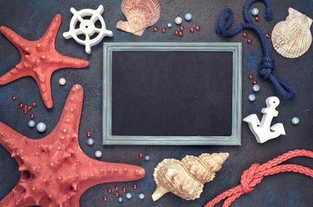 Pizarra en blanco con conchas de mar, cuerda y pez estrella en la oscuridad, copyspace