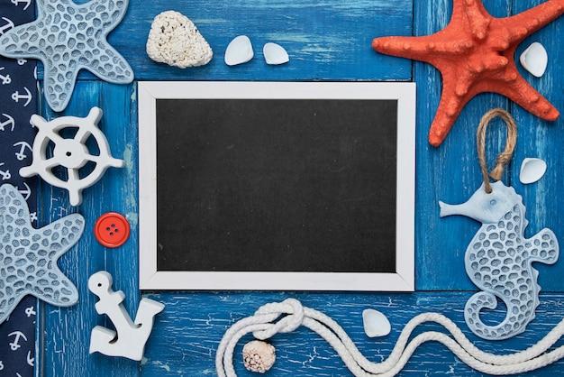 Pizarra en blanco con conchas de mar, piedras, cuerda y pez estrella sobre fondo de madera azul, espacio de copia