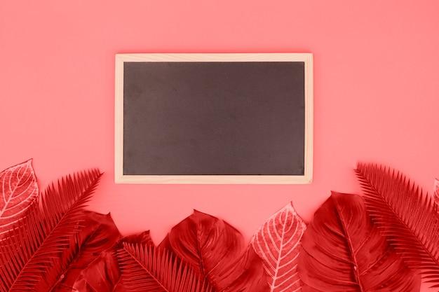 Pizarra en blanco con hojas de coral sobre fondo rosa