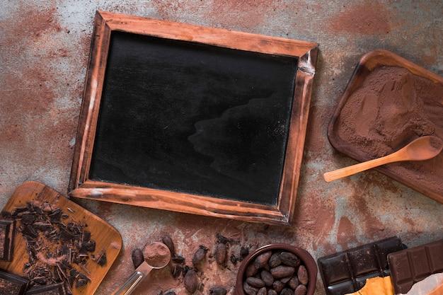 Pizarra en blanco de madera con barra de chocolate, granos de cacao y polvo en mesa rústica