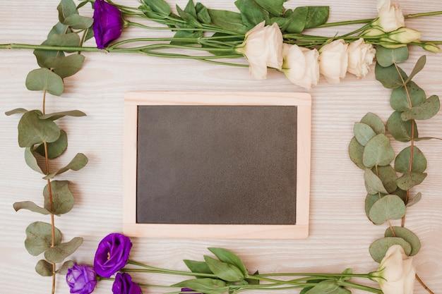Pizarra en blanco de madera decorada con flores de eustoma sobre fondo de madera
