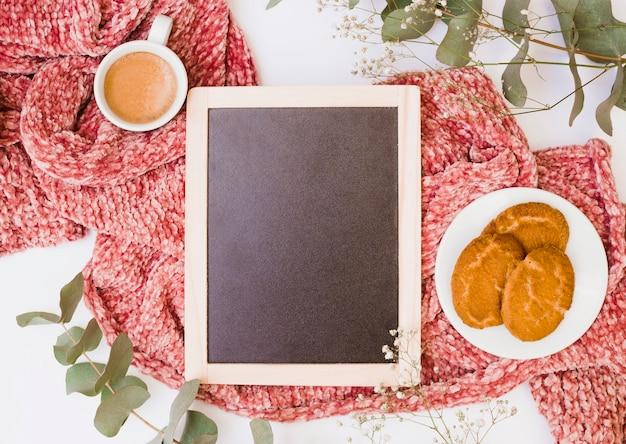 Pizarra en blanco de madera con desayuno en bufanda roja sobre fondo blanco