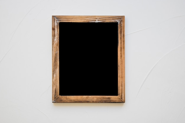 Pizarra en blanco de madera en pared blanca
