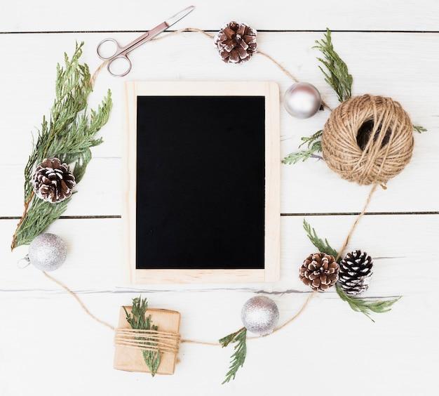 Pizarra en blanco en el marco de la decoración de navidad alrededor