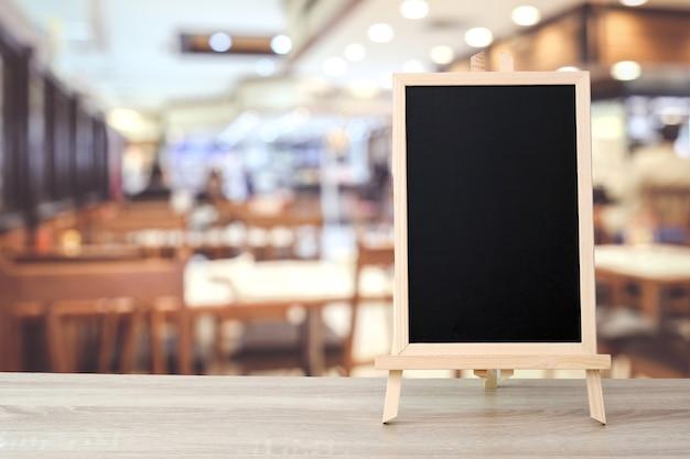 Pizarra en blanco que se coloca en la mesa sobre cafe borroso con fondo bokeh, espacio para texto
