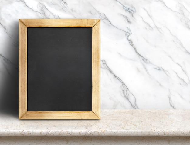 Pizarra en blanco sobre mesa de mármol en la pared de mármol blanco