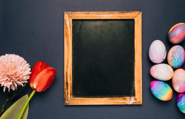 Pizarra en blanco con tulipán rojo; crisantemo y huevos de pascua en fondo negro
