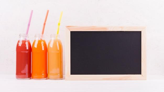 Pizarra y botellas de zumo de colores.