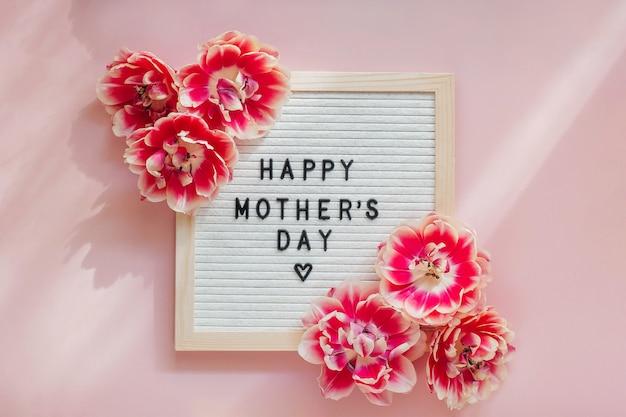 Pizarra con un cartel feliz día de la madre en una mesa rosa con hermosas flores de tulipán.