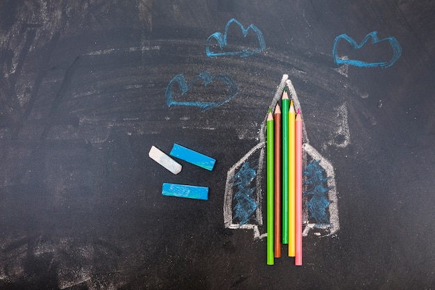 Pizarra con cohete y bolígrafos