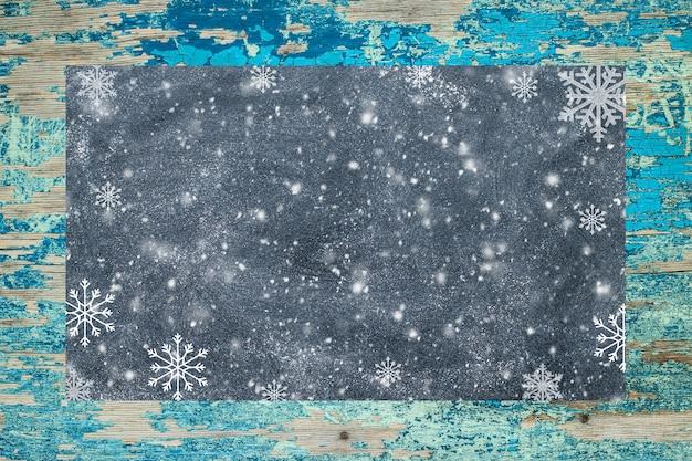 Pizarra con copos de nieve sobre una superficie rústica. concepto de navidad