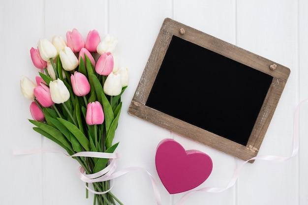 Pizarra con corazón y ramo de tulipanes.