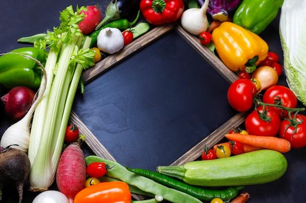 Pizarra con diferentes vegetales saludables coloridos sobre fondo oscuro